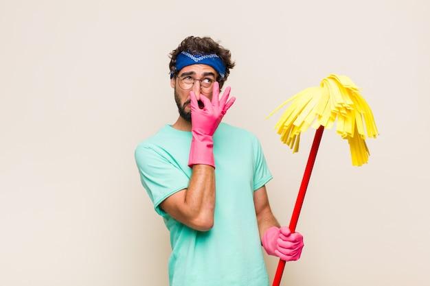 Jovem se sentindo enojado, segurando o nariz para evitar cheirar um fedor desagradável e desagradável