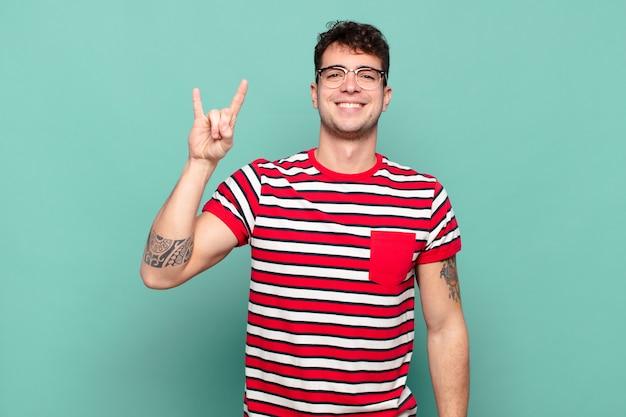 Jovem se sentindo feliz, divertido, confiante, positivo e rebelde, fazendo sinal de rock ou heavy metal com a mão