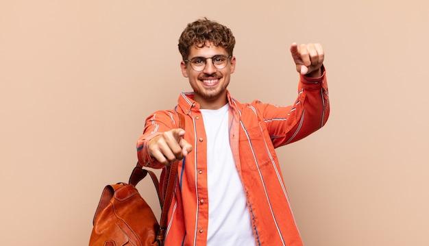 Jovem se sentindo feliz e confiante, apontando para a câmera com as duas mãos e rindo, escolhendo você. conceito de estudante