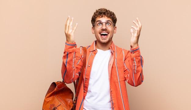 Jovem se sentindo feliz, pasmo, sortudo e surpreso, comemorando a vitória com as duas mãos para cima. conceito de estudante