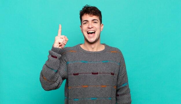 Jovem se sentindo um gênio feliz e animado depois de realizar uma ideia, levantando o dedo alegremente, eureka!