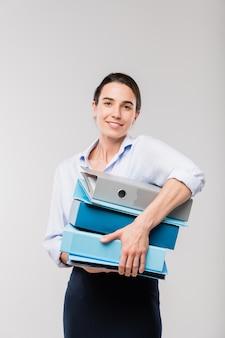 Jovem secretária ou contador de sucesso com uma pilha de pastas com documentos financeiros em frente à câmera