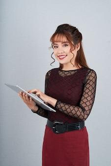 Jovem secretária usando aplicativo móvel sobre o tablet digital permanente contra cinza