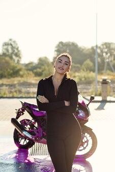Jovem sedutora em um terno preto apertado posa perto de uma motocicleta em um carro self-service