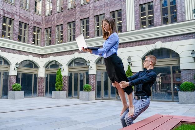 Jovem segura as pernas de uma mulher com roupa de escritório com laptop, conceito de acroyoga para trabalhar como freelancer no fundo do centro de negócios