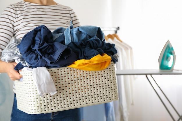 Jovem segura cesta com roupas sujas,