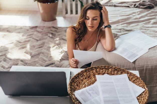 Jovem segura um pedaço de papel e lê, ela trabalha em casa.
