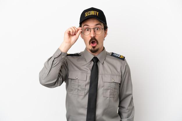 Jovem segurança caucasiano isolado no fundo branco com óculos e surpreso