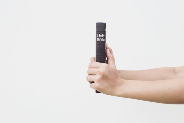 Jovem, segurando a bíblia sagrada nas mãos dela
