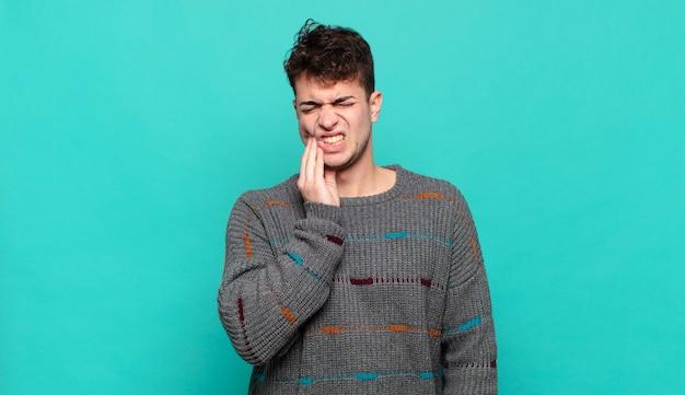 Jovem segurando a bochecha e sofrendo de dor de dente dolorida, sentindo-se doente, miserável e infeliz, procurando um dentista