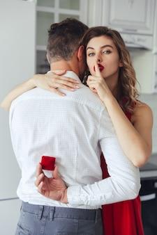 Jovem, segurando a caixa com anel de noivado e sua mulher fazendo gesto de silêncio