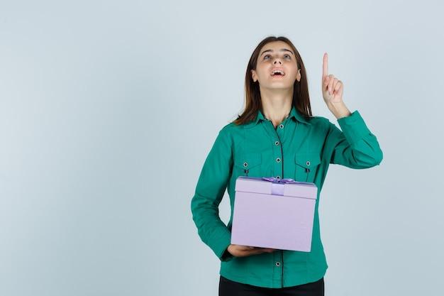 Jovem, segurando a caixa de presente, apontando para cima com o dedo indicador na blusa verde, calça preta e parecendo feliz, vista frontal.