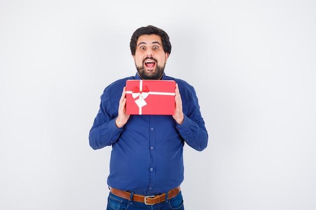 Jovem, segurando a caixa de presente com as duas mãos em jeans e camisa azul e olhando otimista, vista frontal.