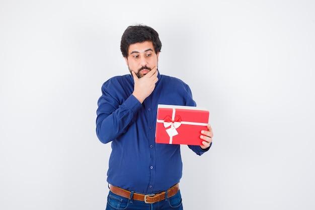 Jovem segurando a caixa de presente e colocando a mão no queixo em jeans e camisa azul e olhando pensativo. vista frontal.