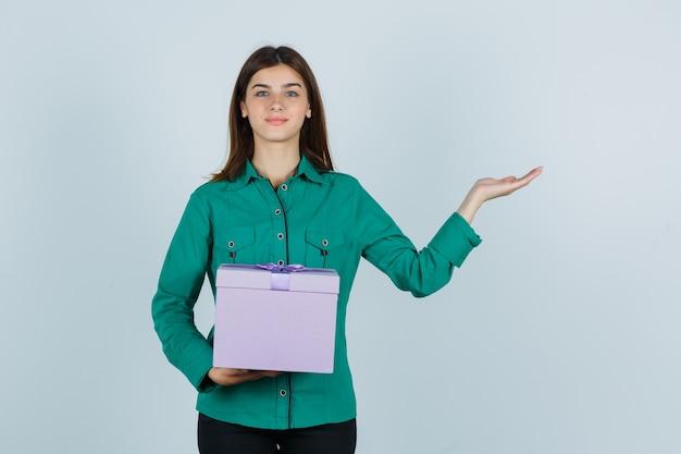 Jovem, segurando a caixa de presente, espalhando a palma da mão na blusa verde, calça preta e parecendo feliz. vista frontal.