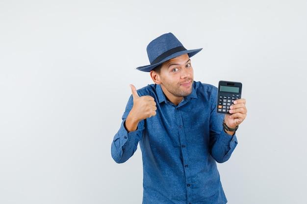 Jovem, segurando a calculadora com o polegar para cima na camisa azul, chapéu e olhando otimista, vista frontal.