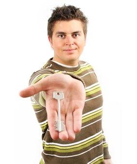 Jovem segurando a chave de prata da casa sobre branco