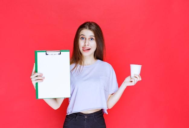 Jovem segurando a folha de relatório e um copo de bebida.