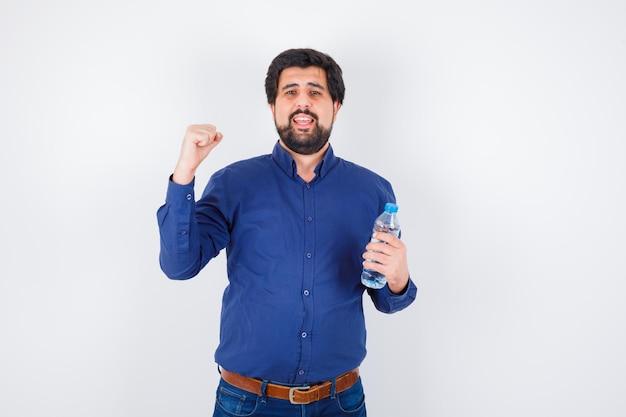 Jovem, segurando a garrafa de água e mostrando o gesto de poder em jeans e camisa azul e olhando otimista, vista frontal.