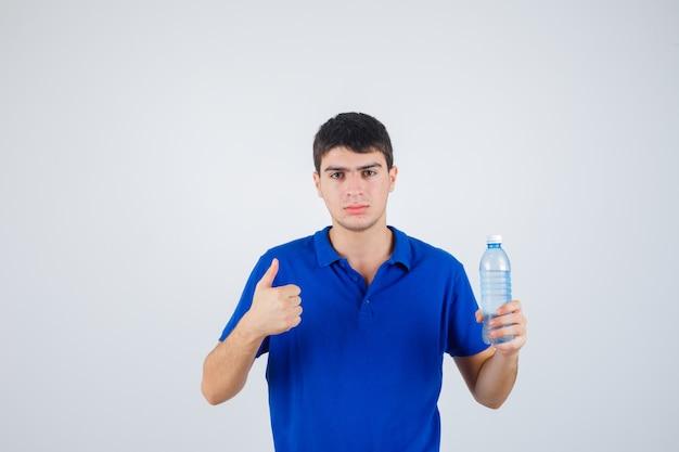 Jovem segurando a garrafa de plástico, aparecendo o polegar em uma camiseta e olhando confiante, vista frontal.