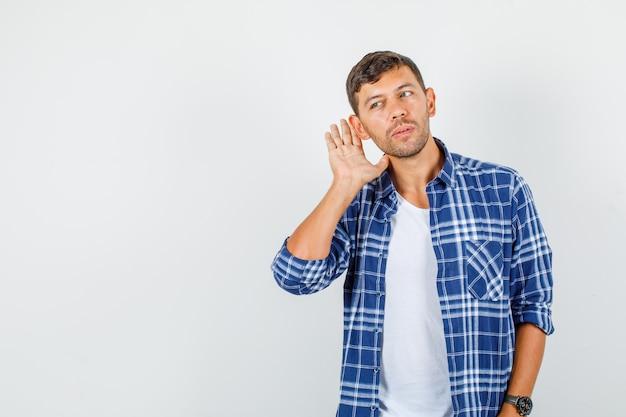 Jovem, segurando a mão atrás da orelha em vista frontal da camisa.