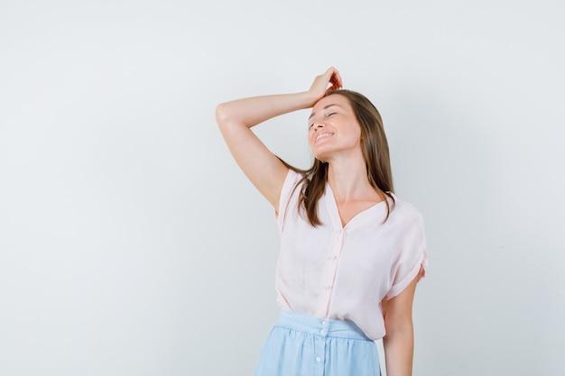 Jovem, segurando a mão levantada na cabeça em t-shirt, saia e parecendo esperançoso, vista frontal.