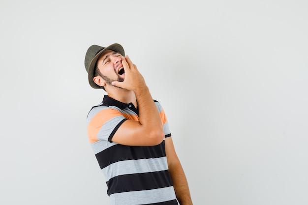 Jovem, segurando a mão na boca enquanto gritava em uma camiseta, chapéu e olhando emocional, vista frontal.