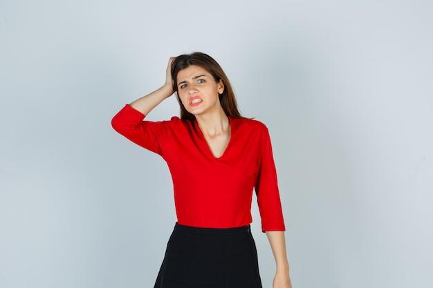 Jovem segurando a mão na cabeça com uma blusa vermelha, saia e parecendo zangada