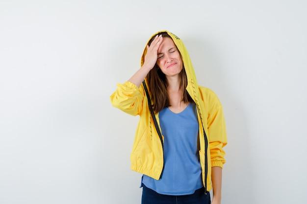 Jovem, segurando a mão na cabeça em t-shirt, jaqueta e olhando triste, vista frontal.