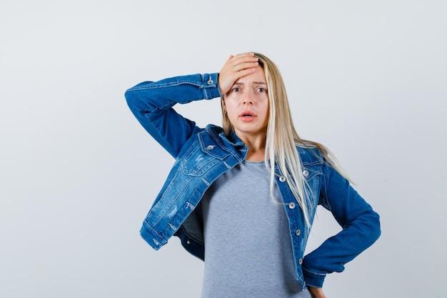 Jovem, segurando a mão na cabeça em t-shirt, jaqueta jeans, saia e parecendo esquecido.
