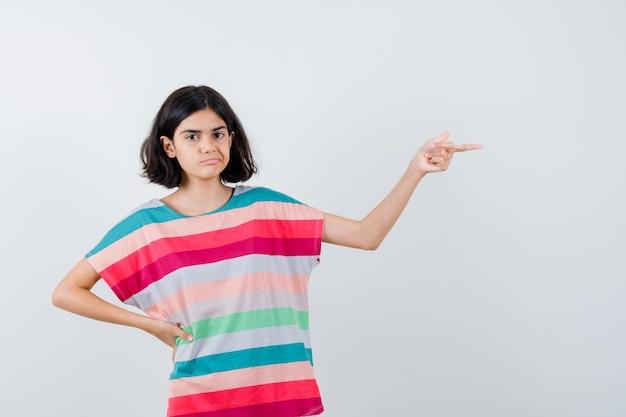 Jovem, segurando a mão na cintura enquanto aponta para a direita em uma camiseta listrada colorida e olhando séria, vista frontal.