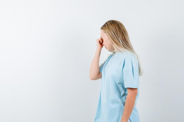 Jovem, segurando a mão no nariz em t-shirt e parecendo exausta, vista frontal.