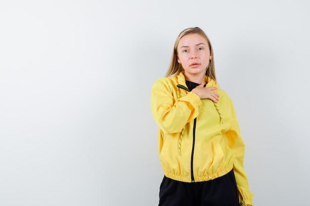Jovem, segurando a mão no peito numa jaqueta amarela, calça e parecendo confiante, vista frontal.