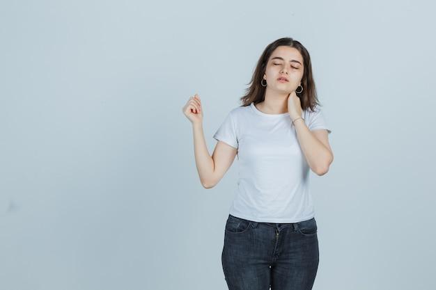Jovem, segurando a mão no pescoço em t-shirt, jeans e parecendo doente, vista frontal.