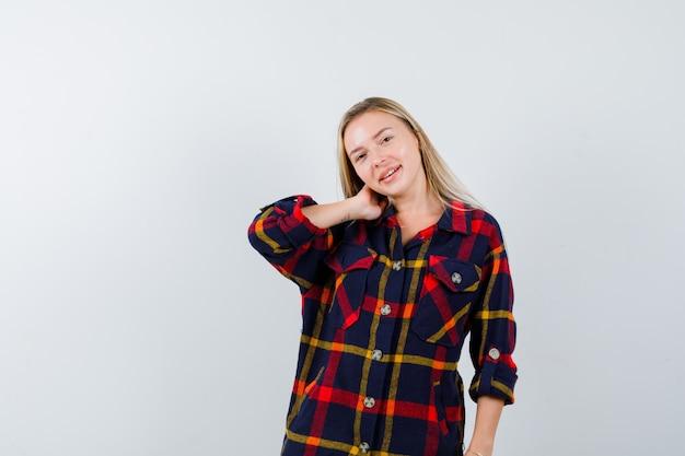 Jovem, segurando a mão no pescoço em uma camisa xadrez e olhando atraente, vista frontal.