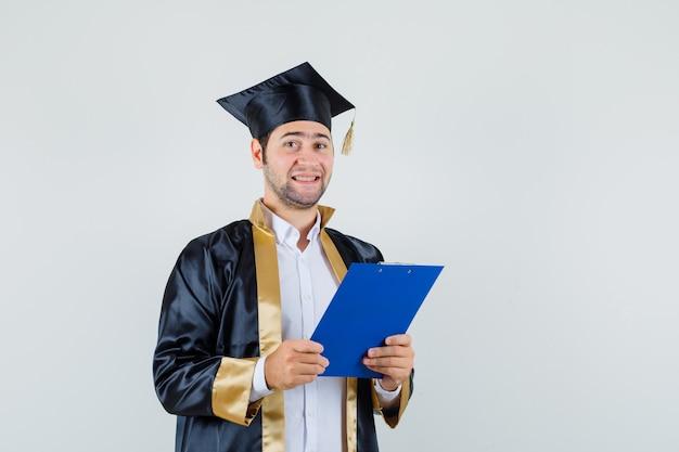 Jovem segurando a prancheta em uniforme de pós-graduação e olhando alegre, vista frontal.