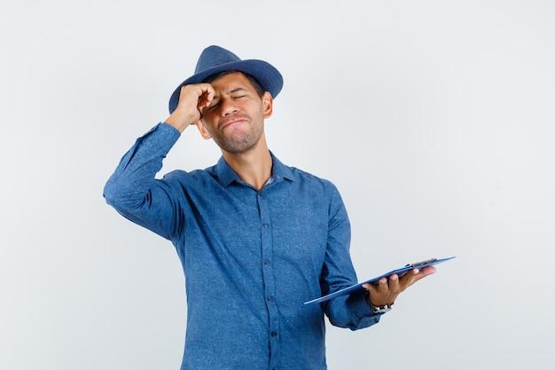 Jovem segurando a prancheta na camisa azul, chapéu e parecendo esquecido, vista frontal.