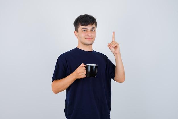 Jovem segurando a xícara de chá, apontando para cima em uma camiseta preta e parecendo confiante. vista frontal.