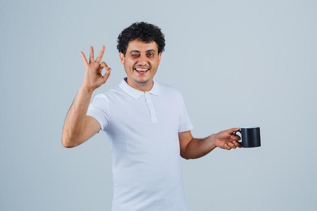 Jovem segurando a xícara de chá enquanto mostra um sinal de ok e piscando em uma camiseta branca e jeans e parece feliz. vista frontal.