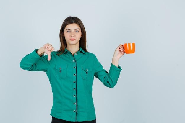 Jovem, segurando a xícara de chá laranja enquanto mostra o polegar para baixo na camisa e parece insatisfeita. vista frontal.