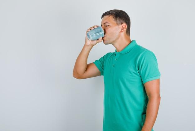 Jovem, segurando a xícara e bebendo uma camiseta verde.
