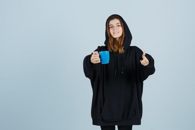 Jovem, segurando a xícara, enquanto aparecendo com um capuz enorme, calças e está linda, vista frontal.