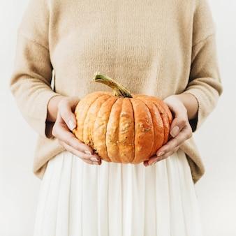 Jovem segurando abóbora de halloween