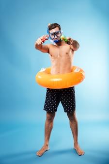 Jovem, segurando armas de água e círculo swimmng