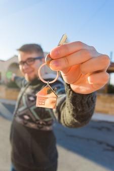 Jovem segurando as chaves de uma casa em um chaveiro em forma de casa na frente de uma nova casa
