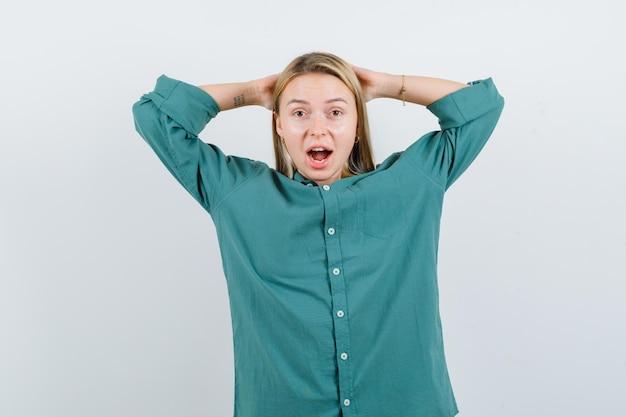 Jovem, segurando as mãos atrás da cabeça em uma camisa verde e parecendo ansiosa.