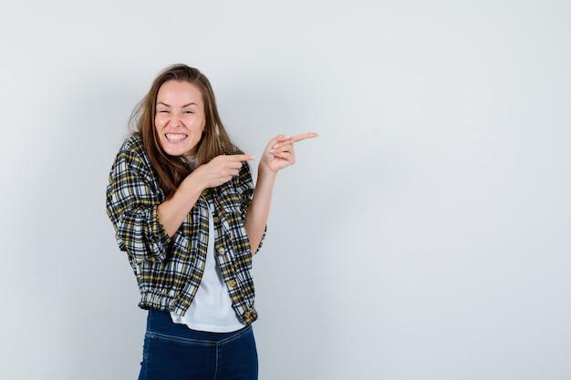 Jovem, segurando as mãos cruzadas no peito em t-shirt, jaqueta, jeans e parecendo feliz, vista frontal.
