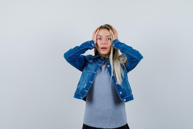 Jovem, segurando as mãos na cabeça em t-shirt, jaqueta jeans, saia e parecendo esquecido.