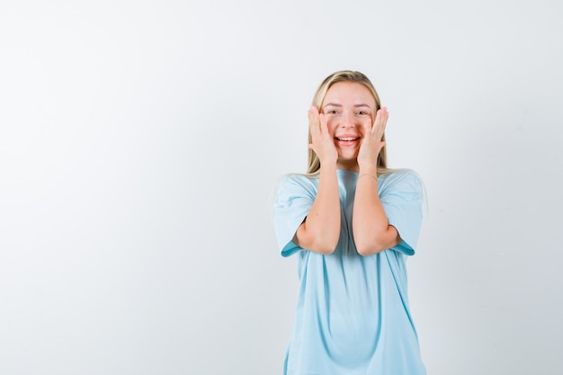 Jovem, segurando as mãos nas bochechas em t-shirt e olhando feliz, vista frontal.