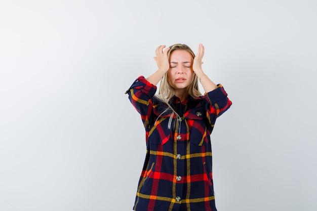 Jovem, segurando as mãos nas têmporas em camisa xadrez e parecendo exausta. vista frontal.